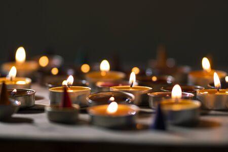 Anzünden einer Kerze auf einem Holztisch. Viele Kerzenflammen in der Dunkelheit.