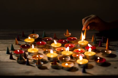 Hand lit lighting candle on wood table. Many candle flames in darkness.