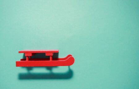 Red sled on neo mint background.Holidays concept. Top view. Flat lay. Stock Photo