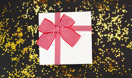 White gift box with red bow on trendy black background with golden glitter. Holiday concept.