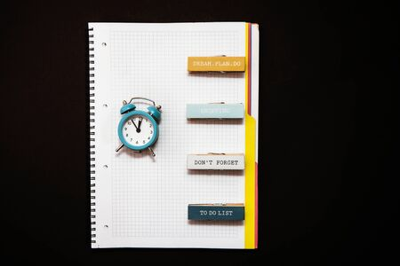 Flat lay blue alarm clock, clean open notebook diary with sticer on dark background top view copy space. Concept time to work, desktop, Office desk, Minimalistic background for blog.