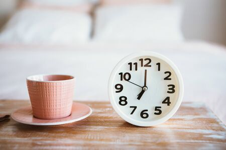 Cup of coffee or tea with white alarm clock near bed. Close up.