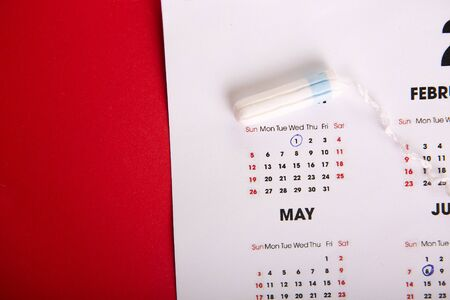 Tampon on a pink background. Menstruation period concept.Hygienic white tampon for women with calendar. Menstruation,protection. Tampons. Menstruation period concept.