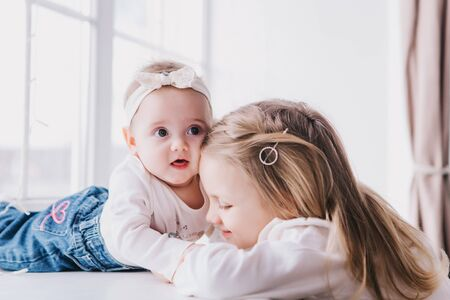 Two cute sisters sitting near window close to each other and playing at home.Little sister hugging her lsmalest sister. Toddler kid meeting new sibling. Family with children at home.