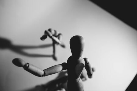 Manipulative Person.Eerie puppeteer hands controlling you on white background.