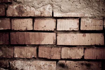 Brick wall was destroyed. Cracked brick photo
