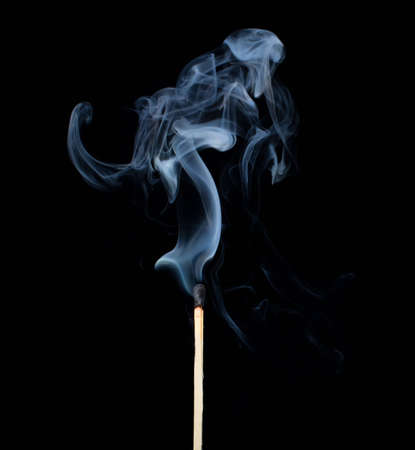Burnt match in a smoke on a black background. photo
