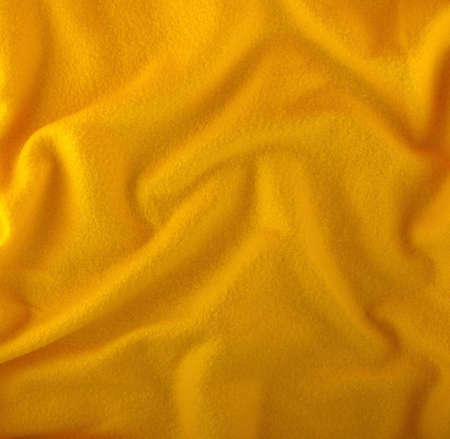 Yellow cloth with folds close photo