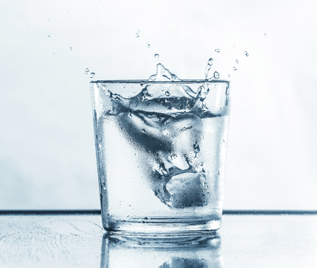 Glass with fresh clear water. Water splashed in a glass.