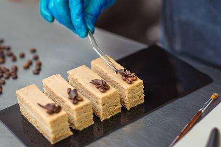 Il pasticcere fa una torta al cioccolato decorata con chicchi di caffè Archivio Fotografico