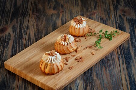Profiteroles with vegetable filling, tomatoes and herbs on a wooden background