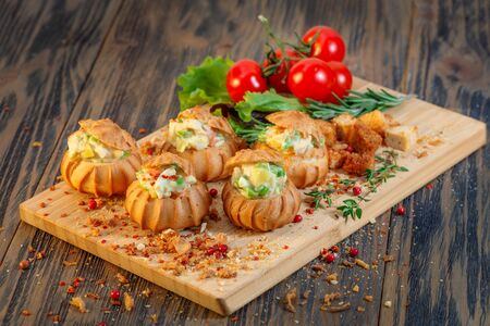 Profiteroles with vegetable filling, tomatoes and herbs on a wooden background Archivio Fotografico