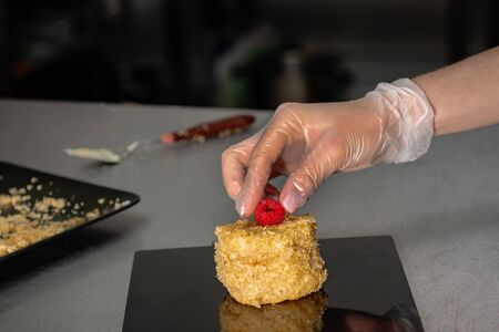 Confectioner in gloves makes a cake with cream and raspberries, sprinkled with crumbs