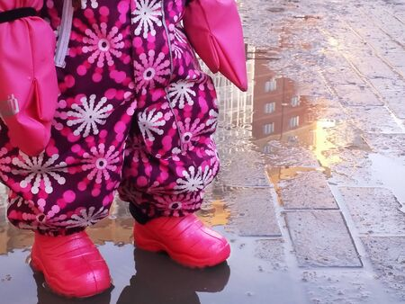 Novosibirsk. Russia. 03.25.2019. Baby girl legs in pink galoshes, overall and part of hands in gloves standing inside a puddle of water on sidewalk of the city in spring.