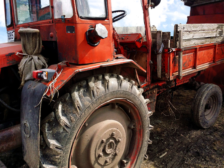 old neglected dark red tractor with rubber dirty wheels Imagens