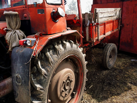 Close-up of old neglected dark red tractor with rubber dirty wheels
