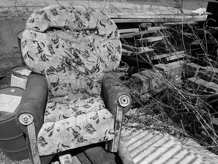 old broken armchair at the dump with boards
