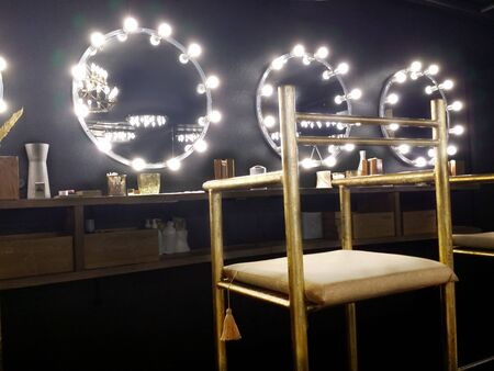 Atmospheric black interior in the beauty salon. High golden, shabby chair in the foreground. Mirror with light bulbs. Place for make up. Banque d'images - 124887761