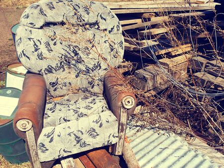 old dirty brown broken armchair at the dump with boards, barrels and rusty pipes. Vintage style. Reklamní fotografie
