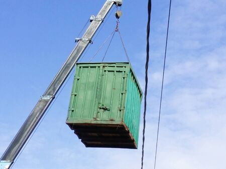 Green cargo container which gray boom with blue hook of truck manipulator lift up near the power line Banque d'images