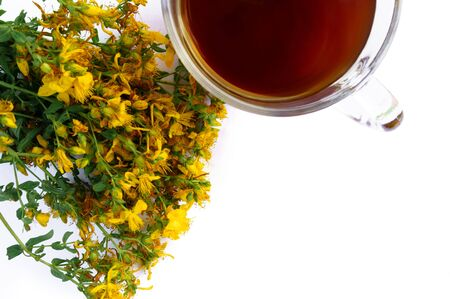 Cup of tea and yellow Hypericum flowers out of focus in background isolated on white background with free space for text Banque d'images