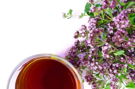 Tea in glass with defocused bouquet of marjoram isolated on white background with free space for text
