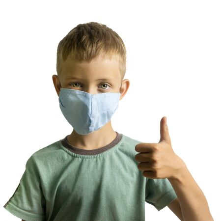 Boy 6-7 years old in green t-shirt and a blue medical mask on his face with thumb up looks at the camera
