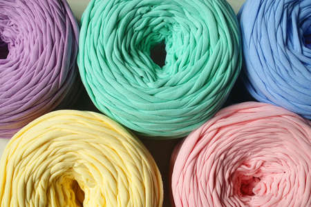 Top view of colorful blue, pink, yellow, lilac, minty bobbins of t-shirt yarn for hand knitting Banque d'images
