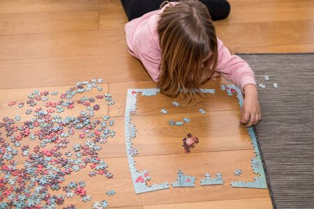 Blond girl in a pink sweater playing with a jigsaw on the floor by the confinement of coronavirus covid-19