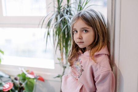 blonde girl with blue eyes and pink sweater confined to the house and sad because she can't go outside to play Reklamní fotografie