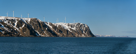 Wind Energy in Norway. The blue sea and gray cliff covered with snow on the background of a cloudless sky photo