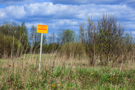 dig: Warning sign in a field. It is forbidden to dig