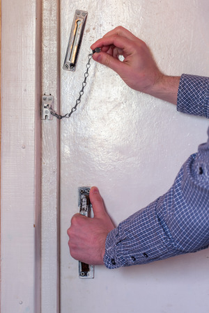 safety lock: White door, old chain, male hands. The man opens the door, opens chain Stock Photo