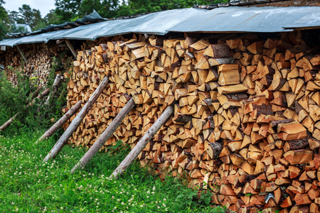 neatly stacked: Several neatly stacked firewood in the village courtyard. On props. Country yard with store of wood