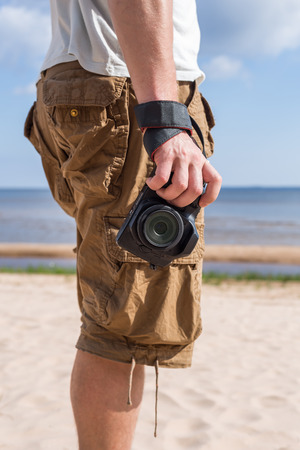 breeches: Man male dressed in shirt and breeches, standing on the sandy shore of the sea and holding a camera. Vertical orientation Stock Photo
