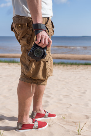 breeches: Man male dressed in shirt and breeches, red shoes, standing on the sandy shore of the sea and holding a camera Stock Photo