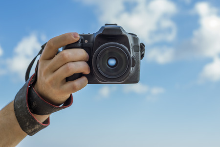 focus: Man holding a camera on a background of blue sky with clouds. Stock Photo