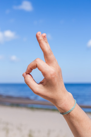 samadhi: Female hand: fingers in the form of yogic gesture against the blue sea and sky.