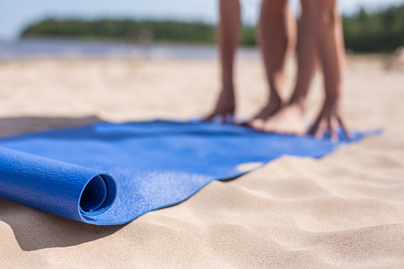 yoga white: Blue mat and blurred in the background hands and feet. Girl doing yoga on a sunny day at the beach.