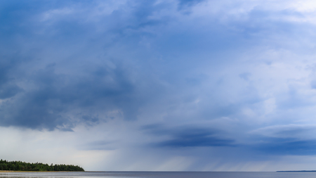 torrential: Torrential rain over the lake. Beautiful clouds various shades Stock Photo