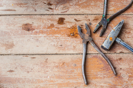old tools: Old tools hammer and pliers lie on the shabby boards