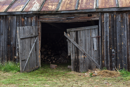 farm building: Abandoned barn in a village with a rusty roof and wood inside