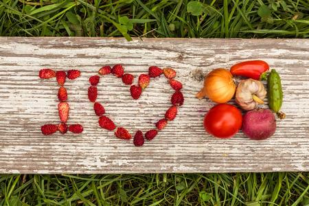 Gezond dieet. Aardbeien zijn opgenomen in de letters gelegd op een achtergrond van groen gras en karton. Stockfoto
