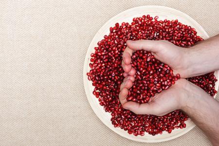 frutas tropicales: Plato lleno de semillas de granada pelada y un hombre que sostiene en forma de corazón
