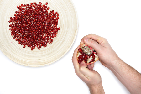 Full plate of peeled pomegranate seeds and a man de-seeding fruit