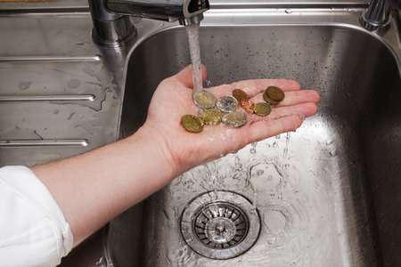 laundry concept: man washing coins under running water Stock Photo
