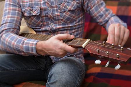 musico: Joven músico pone en marcha una pequeña guitarra.