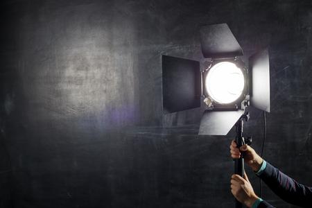 Fotograaf past verlichtingsapparatuur aan op een achtergrond van schoolbord Stockfoto - 51337907