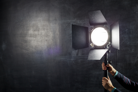 Photographer adjusts lighting equipment on a background of chalkboard Archivio Fotografico