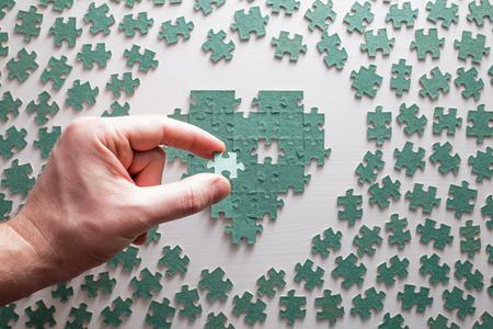 Silhouette del cuore costituito da pezzi di puzzle, con un buco nel mezzo